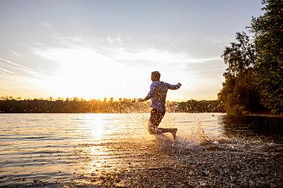Man running into lake by sunset - p300m2041853 von Jo Kirchherr