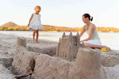 Sand castle and mother with daughter on the beach - p300m2143631 by Daniel Ingold