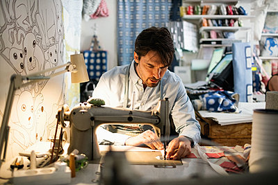 Serious owner sewing fabric at shop - p426m1179382 by Maskot