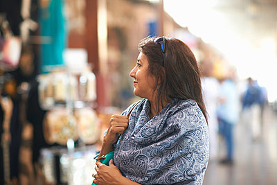 Mature female tourist looking at market stall, Sharjah, United Arab Emirates - p429m1407796 by Peter Muller