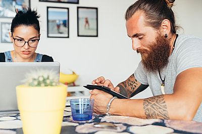 Bearded tattooed man with long brunette hair and woman with long brown hair sitting at a kitchen table, using laptop and mobile phone. - p429m2202013 by Eugenio Marongiu