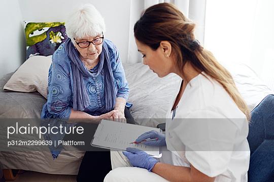 Nurse with elderly woman at home - p312m2299639 by Plattform