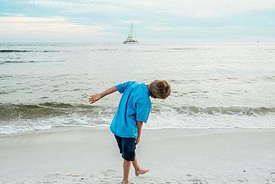 Rear view of playful boy bending at Panama City Beach against sky - p1166m1485614 by Cavan Images