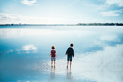 Rear view of brothers playing in lake at forest - p1166m2060341 by Cavan Images