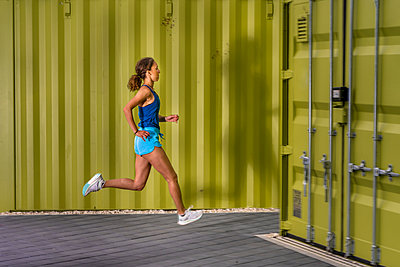 Young woman jogging on pavement in front of cargo containers - p300m2132513 by Stefan Schurr