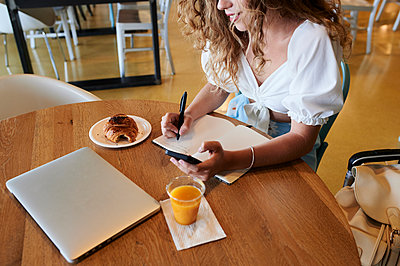 Young woman in a cafe using smartphone and taking notes while having breakfast - p300m2140467 by Ivan Gener