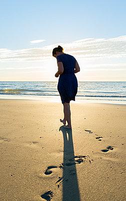 Mid adult woman making footprint in sand at coast, Westkapelle, Zeeland, Netherlands - p429m958489f by Mischa Keijser