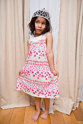 Little girl stands holding her pretty pink floral dress wearing a tiara - p5350220 by Michelle Gibson