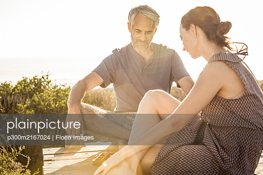 Couple sitting on boardwalk at the coast playing backgammon - p300m2167024 by Floco Images