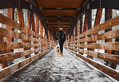 Teenage girl walking dog across snowy wooden covered bridge. - p1166m2084590 by Cavan Images