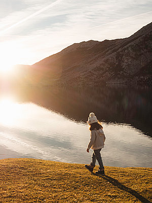 Girl walking near a lake with mountain - p1522m2150684 by Almag