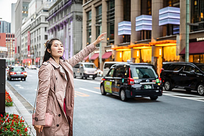 Young woman hailing a taxi at a street in Ginza, Tokyo, Japan - p300m2140606 by 27exp