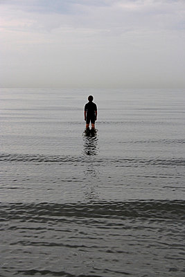Looking towards a silhouette of a boy standing in the sea in Sussex - p3313104 by Gail Symes