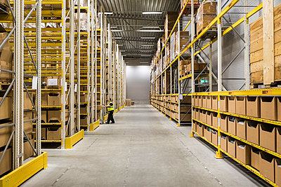 Full length of mature female warehouse worker pushing cart on aisle in industrial building - p426m2018848 by Maskot