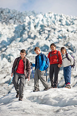 Family walking on glacier - p429m727002f by Henn Photography