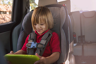 Girl in car safety seat looking at digital tablet - p924m1404201 by Kinzie Riehm