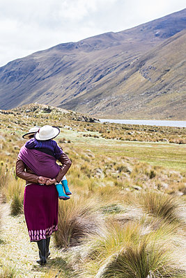 Woman carrying a child in the mountain in Ecuador - p940m1480768 by Bénédite Topuz