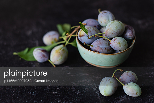 Close up image of a bowl of fresh plums against a black background. - p1166m2207952 by Cavan Images