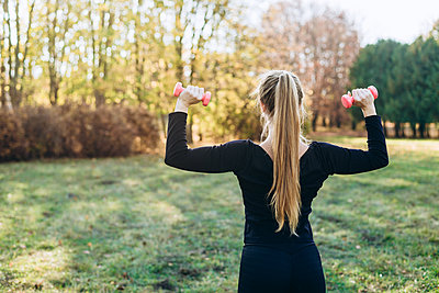 Fitness in the park, girl holding dumbbells, back view. - p1166m2171872 by Cavan Images