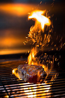 Beautiful grilled steak with sparks of fire - p1166m2189900 by Cavan Images