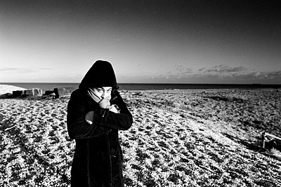Woman on shore freezing - p2686348 by James Wadey