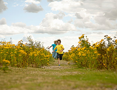 Boys running in field of flowers - p429m1450385 by Seb Oliver