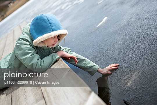 Teen girl lying on the bridge near lake and touching ice - p1166m2269618 by Cavan Images
