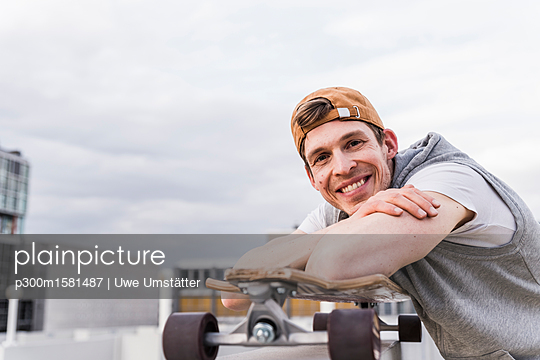 Portrait of smiling man with skateboard leaning on a wall - p300m1581487 von Uwe Umstätter