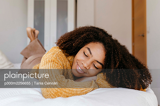 Young woman smiling while lying on bed at home - p300m2256655 by Tania Cervián