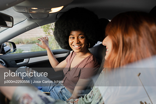 Afro woman smiling while looking at female friend in car - p300m2293556 by Jose Carlos Ichiro