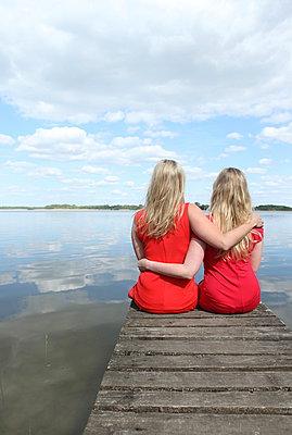 Arm in Arm auf dem Steg sitzen - p045m931639 von Jasmin Sander