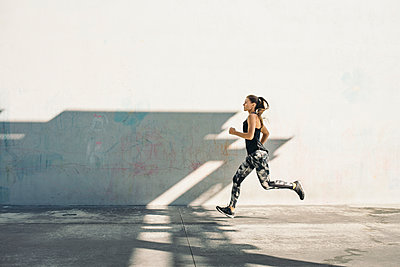 Full length side view of female athlete running on sidewalk against white wall - p1166m1415129 by Cavan Images