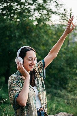 Happy woman dancing while enjoying music in public park - p300m2207106 by Xavier Lorenzo