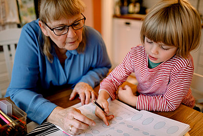 Grandmother assisting grandson in doing homework - p426m2195070 by Maskot
