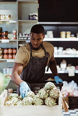 Male entrepreneur arranging food product in basket at delicatessen shop - p426m2270676 by Maskot