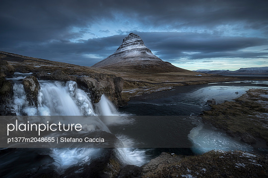 Iceland, West Iceland, Vesturland, Snæfellsnes, First lights over Witch hat Mountain or Kirkjufell Mountain and Kirkjufelfoss Waterfall, Iceland - p1377m2048655 by Stefano Caccia