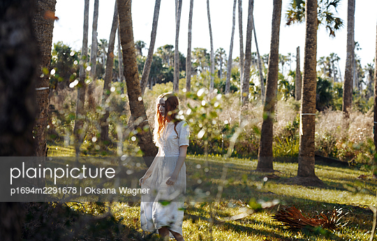 Serene red-haired young woman in a delicate dress walking alone in a sunny forest  - p1694m2291678 by Oksana Wagner
