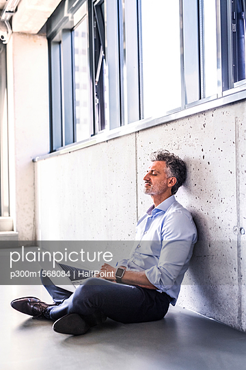 Mature businessman with laptop sitting on the floor leaning against the wall - p300m1568084 by HalfPoint