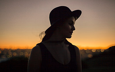 Young woman with hat at sunset - p1324m1165221 by michaelhopf