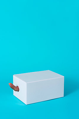 man's forefinger popping from a hole in a white cardboard box on a blue background - p1423m2076790 by JUAN MOYANO