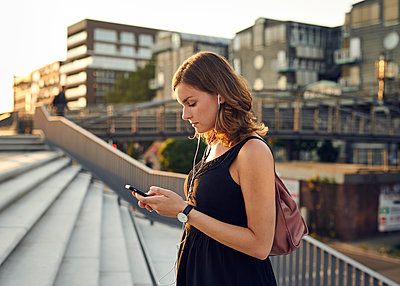 Germany, Young woman with smart phone exploring Hamburg - p300m1192279 by Willing-Holtz