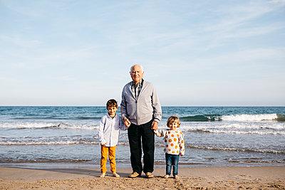 Portrait of happy grandfather standing hand in hand on the beach with his grandchildren - p300m2103167 von Josep Rovirosa