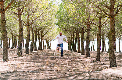 Man running with his dog in a park - p300m2166626 by Daniel González