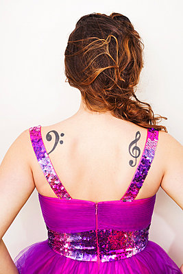 Rear view of a young woman with musical tattoos on back - p429m801595 by Patryce Bak