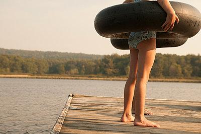 Caucasian girls with inner tubes on wooden dock - p555m1454161 by Jon Feingersh