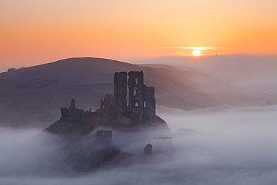 Mist below Corfe Castle at Sunrise, Dorset, England - p651m2007167 by Tom Mackie