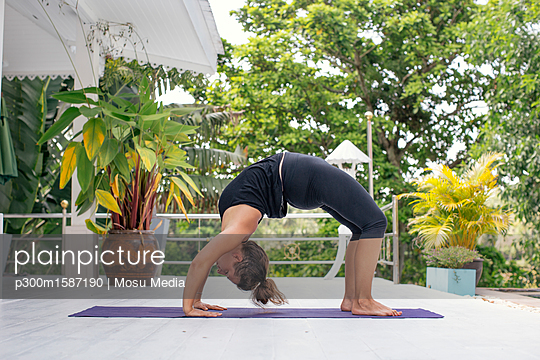 Woman practicing yoga on terrace - p300m1587190 von Mosu Media