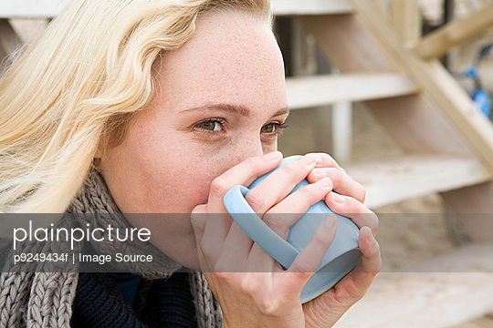Woman having warm drink - p9249434f by Image Source