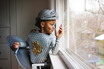 Curious boy dressed up in armor costume looking out through window at home - p1166m1140353 by Cavan Images