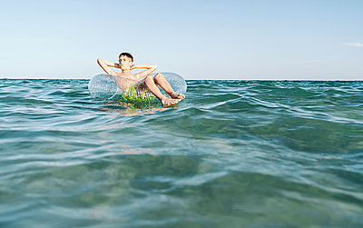 relaxed white boy swimming in a float in the sea enjoying calm waves in summertime - p1166m2213134 by Cavan Images